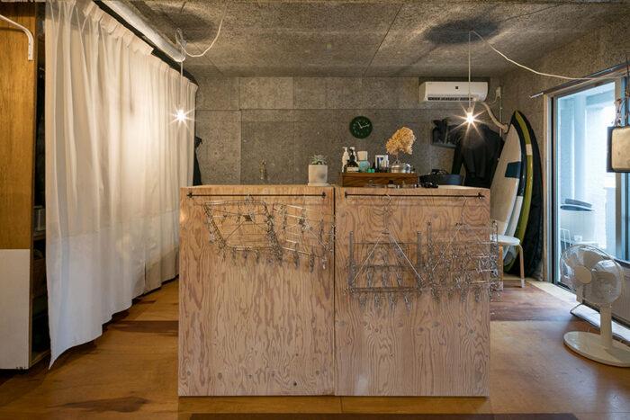 拓也さんのベッドスペースには、サーフィン、スノーボードとアウトドアスポーツの道具も。空間をゆるやかに分ける、DIYで作った収納棚は可動式。
