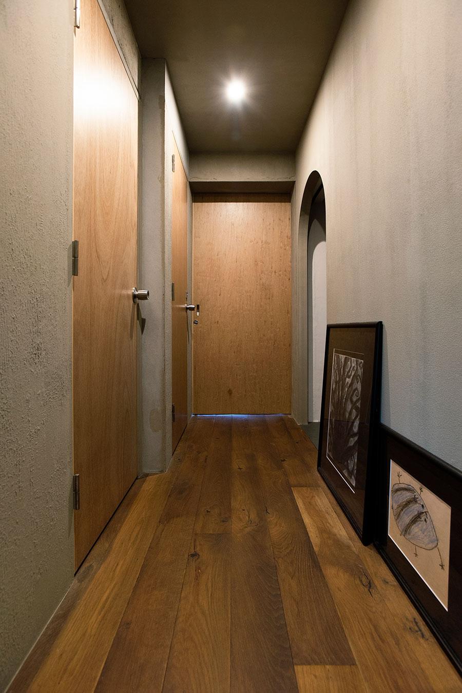 カチオンの塗り壁の廊下を挟んでWIC、ストレージ、トイレが。床上のアートは彼女が描いたもの。