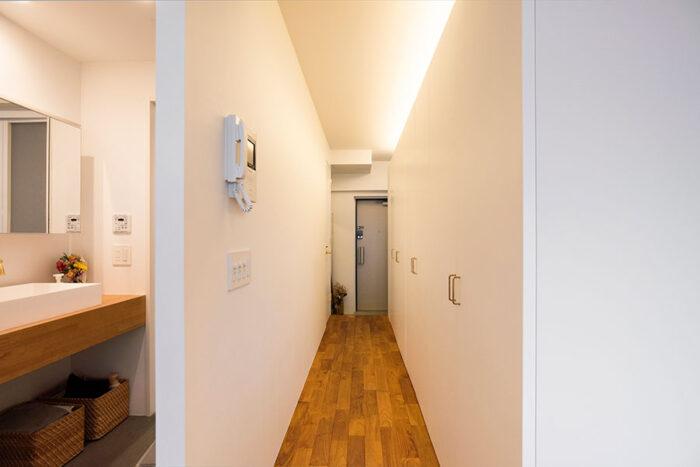 収納がベッドルームとの仕切りに。天井は塞がず開けて上部に間接照明を施した。収納の取っ手を引くと、クローゼット、ストレージ、洗濯機が現れる。