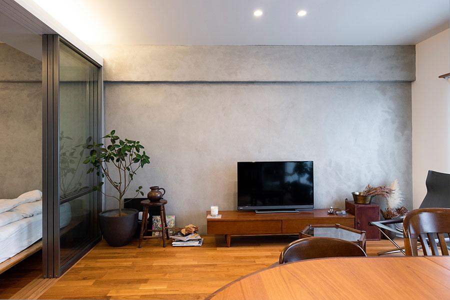 リビング〜ベッドルーム〜ワークスペースの一連の壁をモルタル塗装で。チークの床に馴染むTVボードはACME Furnitureで購入した。