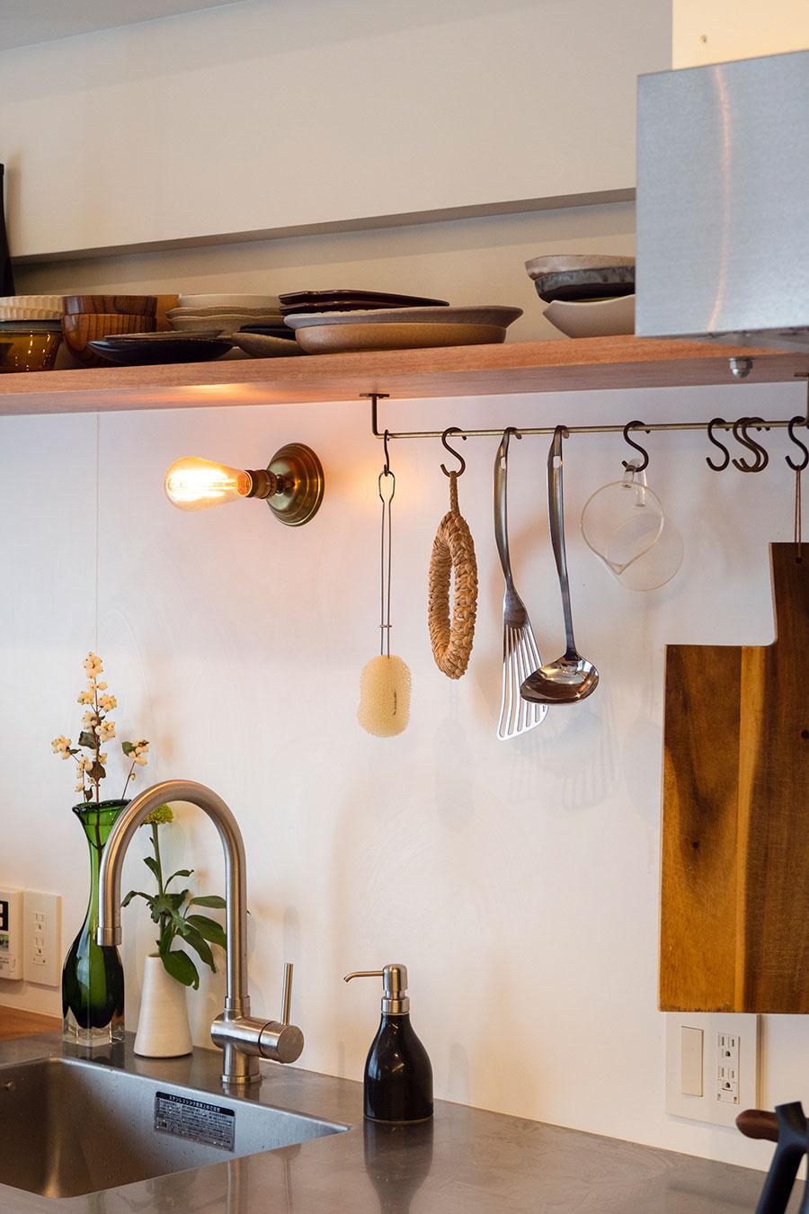 """造作の棚板で、お気に入りの陶器の器を""""見せて""""収める。棚板下のtoolboxの真鍮バーはDIYで設置。"""