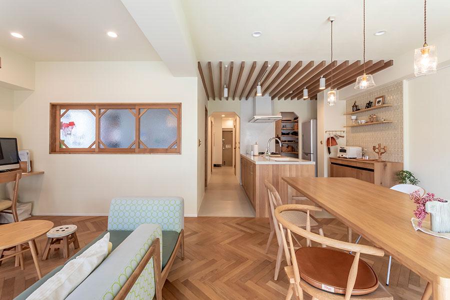 リビング床のヘリンボーンと対になるように貼られたルーバー天井。