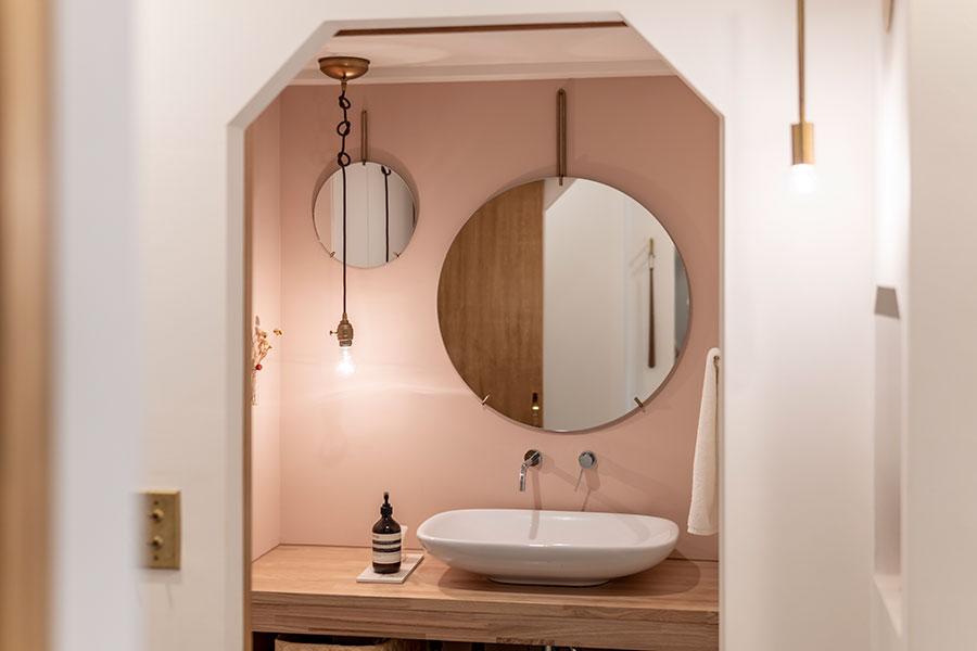 ピンクの壁紙と真鍮で吊るされた丸い鏡が印象的な洗面所。