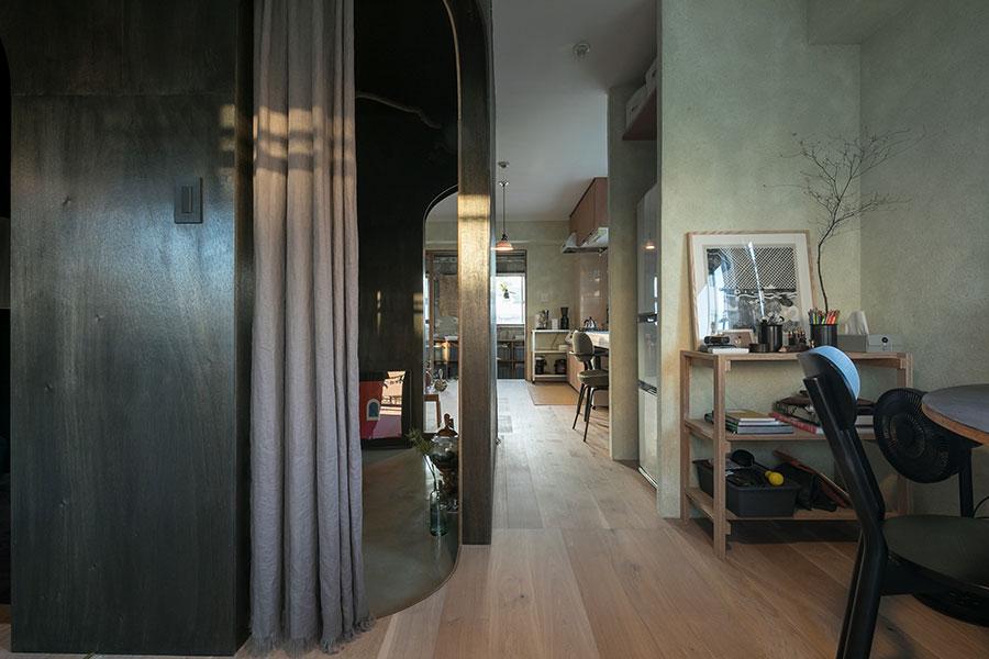 グリーンがかったシルクプラスターの壁や、柔らかなリネンのカーテンが空間の印象を和らげる。