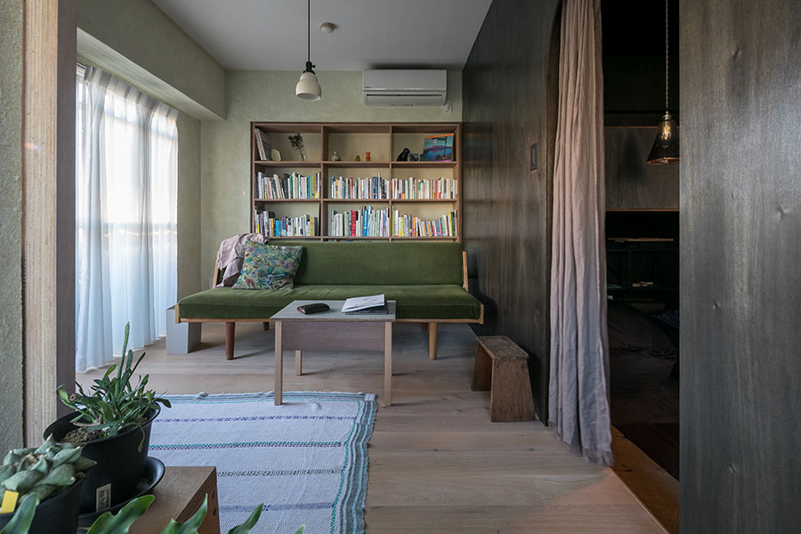 ハンス・J・ウェグナーのヴィンテージソファのある空間は、背面に本棚を作った。