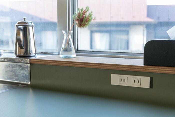 キッチンの天板とひとつながりのリノリウムのデスクの天板はRをつけ、コンセントを設置。